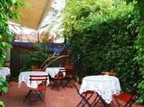 מסעדה עם מטבח קטן, שולחנות ספורים וגינה חמודה
