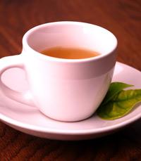 כפית של תערובת צמחי מרפא על כוס מים רותחים
